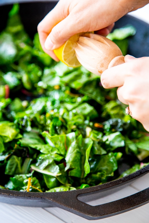 A hand squeezing lemon juice with a wood juicer into chard.