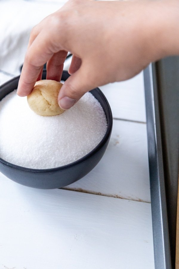 A hand rolling a ball of cookie dough in granulated sugar.