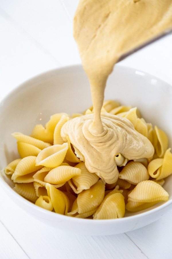 Cheese sauce being poured over pasta shells in a white bowl.