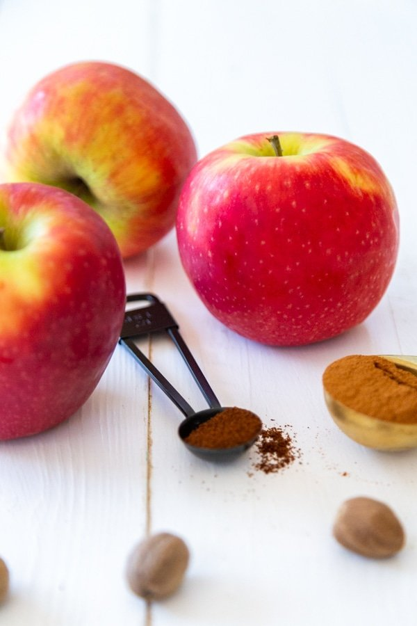 3 red apples and spices in measuring spoons and whole nutmeg on a white wood table.