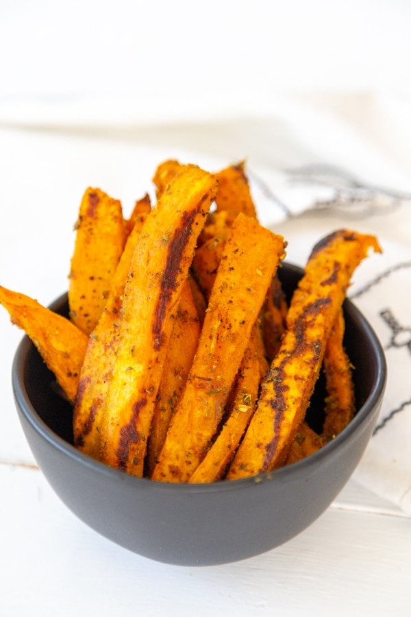 A black bowl filled with sweet potato fries.