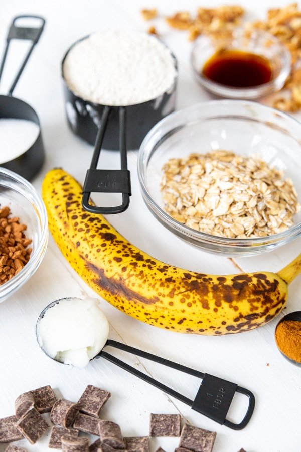 A banana, a bowl of oats, and measuring cups with flour and other ingredients for cookies.