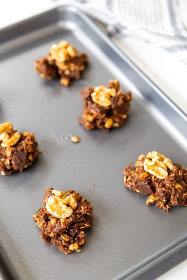 Chocolate cookie dough balls with a walnut in the center of each one on a baking sheet.