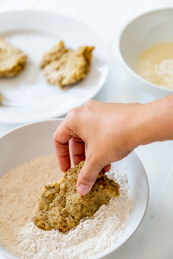 A hand dipping a chicken cutlet in a bowl of flour.