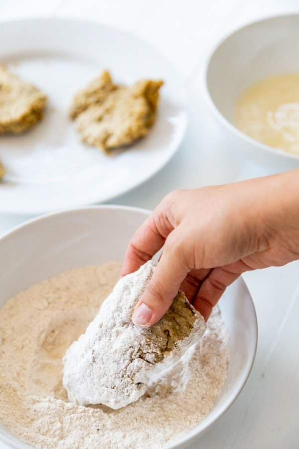 A hand dipping a chicken cutlet coated in flour and egg in more flour.