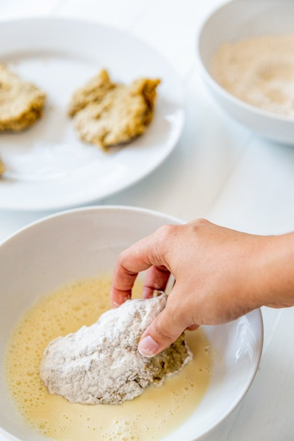 A hand dipping a floured chicken cutlet in a bowl of eggs.