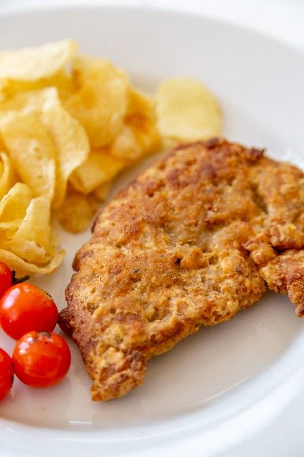 A piece of fried chicken, potato chips, and tomatoes on a white plate.
