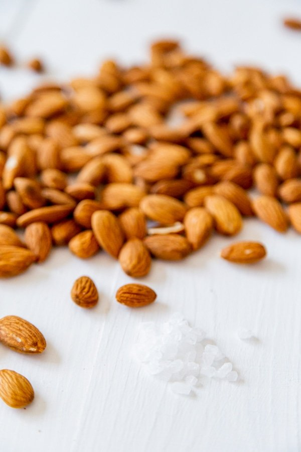 A pile of almonds and sea salt on a white wood surface.