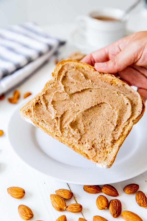 A hand holding a piece of toast with almond butter over a white plate with almonds scattered around it.