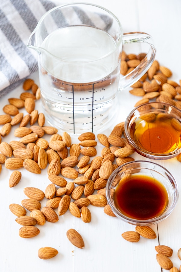 A measuring cup with water and almonds and a glass bowl of vanilla and maple syrup next to it.
