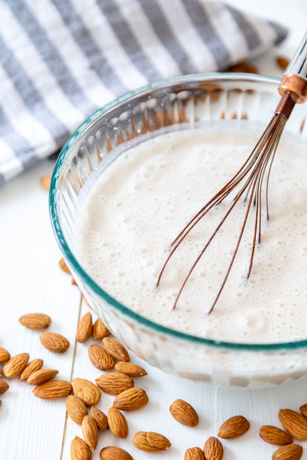 A glass bowl filled with almond milk and maple syrup and vanilla being whisked together.