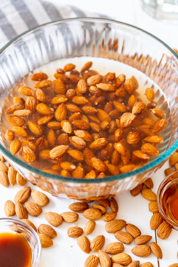 Almonds in a bowl of water with almonds scattered next to the bowl.