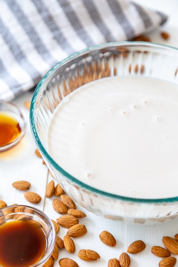 A glass bowl filled with almond milk with almonds scattered next to it.