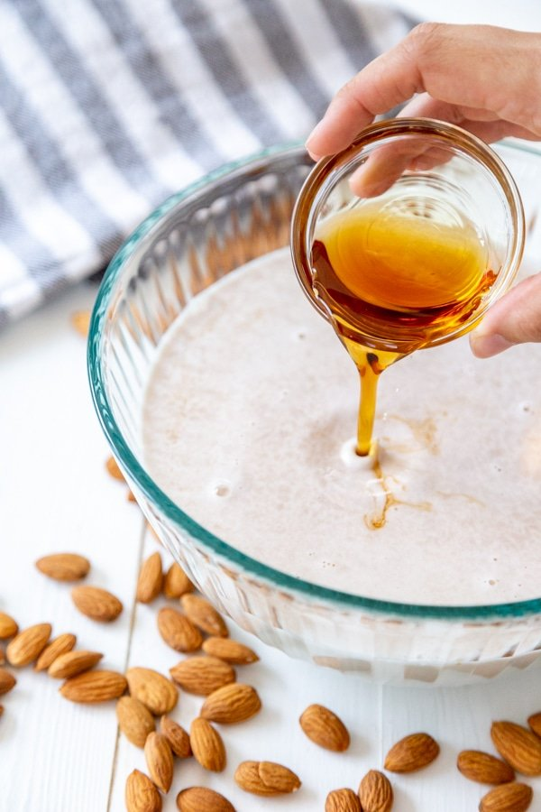 A glass bowl filled with almond milk with a hand pouring maple syrup into it.