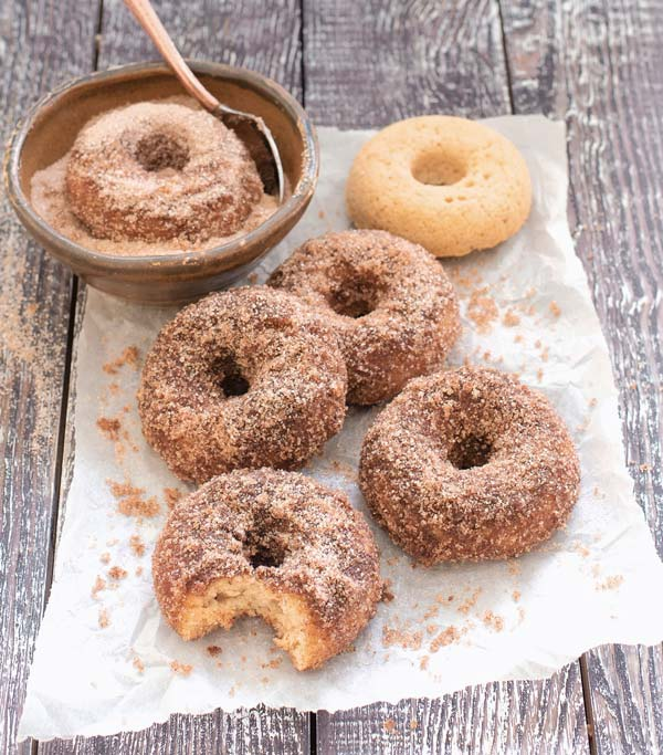 A pile of sugar doughnuts on parchment paper.