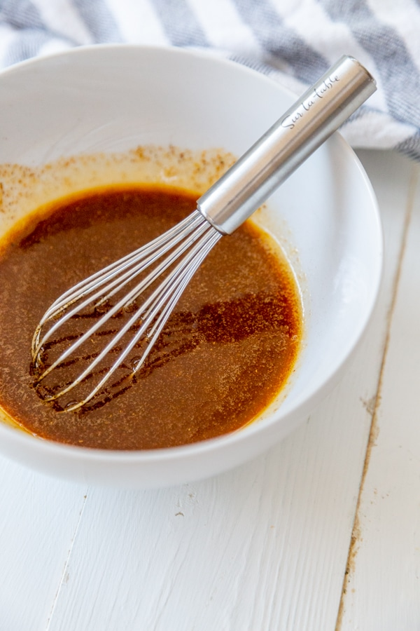 A white bowl with red sauce and a whisk.