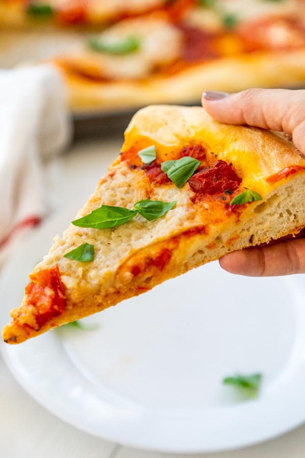 A hand holding a slice of homemade pizza with cheese and basil.