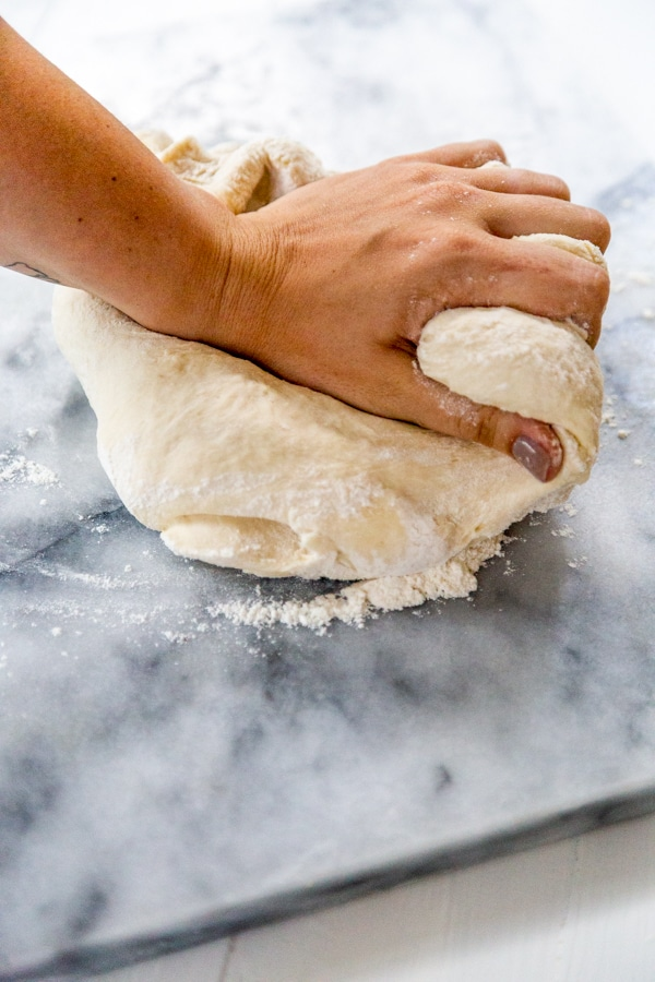 A hand kneading a ball of pizza dough on a marble slab.