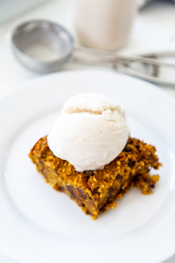 A chocolate chip blondie on a white plate with a scoop of ice cream on top.