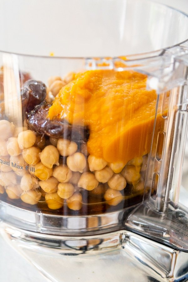 A food processor with chickpeas, pumpkin puree, dates and spices.