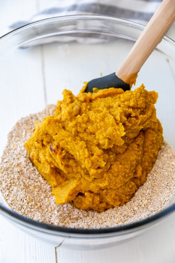 A glass mixing bowl with oat flour and a spatula with pumpkin puree.