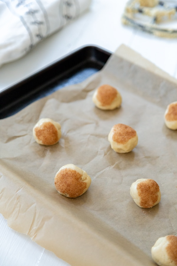 A parchment lined cookie sheet with balls of cookie dough topped with cinnamon sugar.