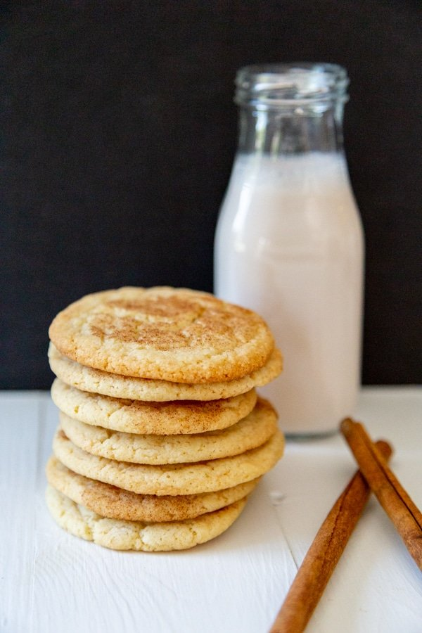 A stack of cookies and a bottle of milk with cinnamon sticks next to it.