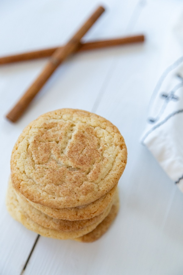 A stack of cookies with cinnamon sugar on top and cinnamon sticks on a white wood table.