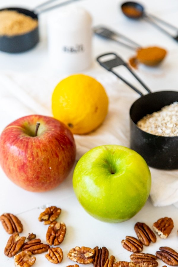 Apples, pecans, oats, and spices on a white wood table.