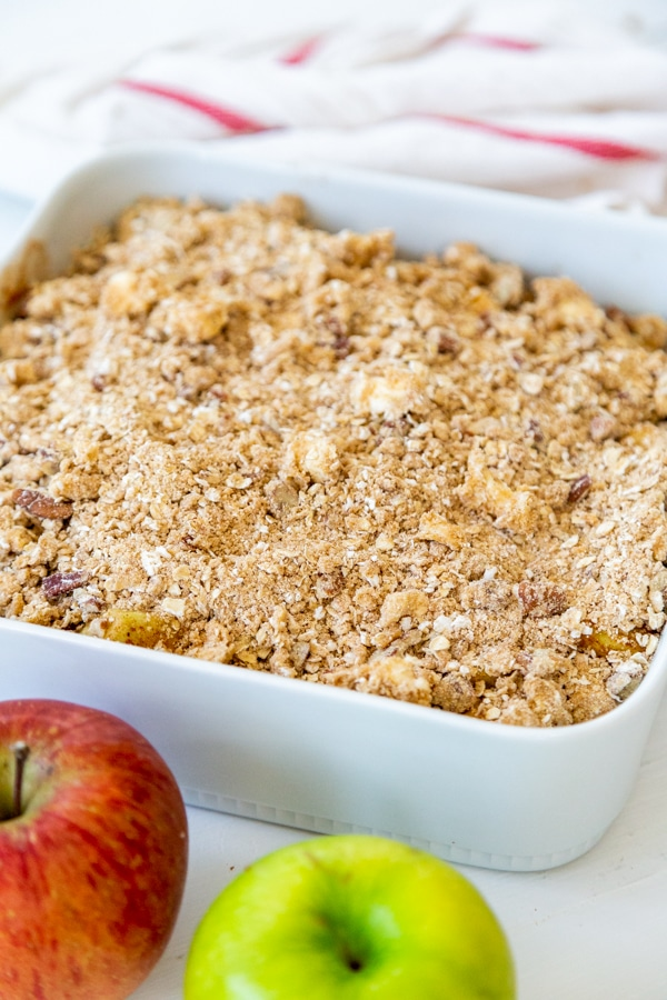 A white dish with unbaked apple crisp.