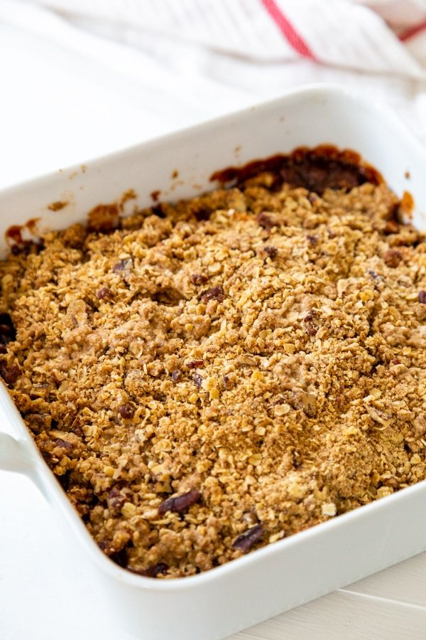 A square white pan with apple crisp in it.