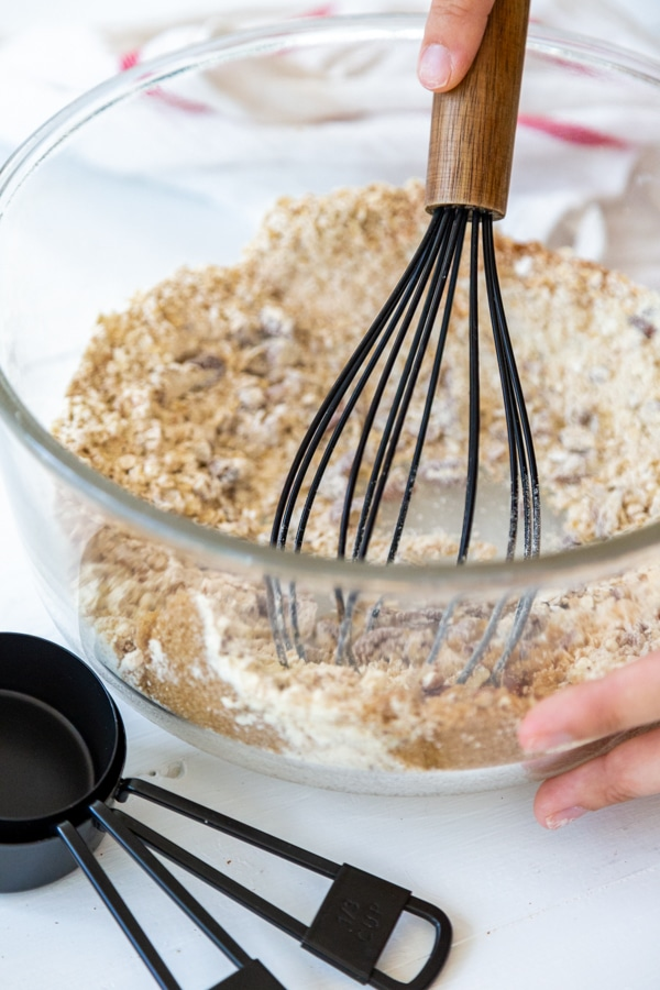 A glass bowl with oats, flour, and spices being whisked together.