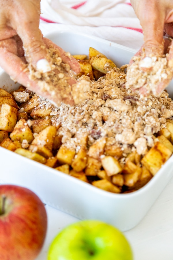Two hands putting apple crisp topping over a dish of apple filling.