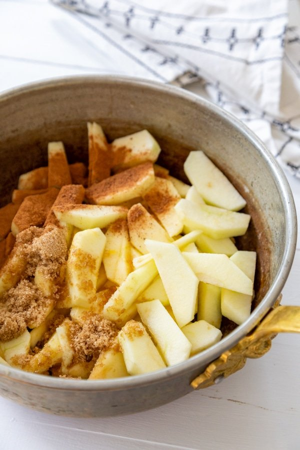 A copper pot with sliced apples and cinnamon.