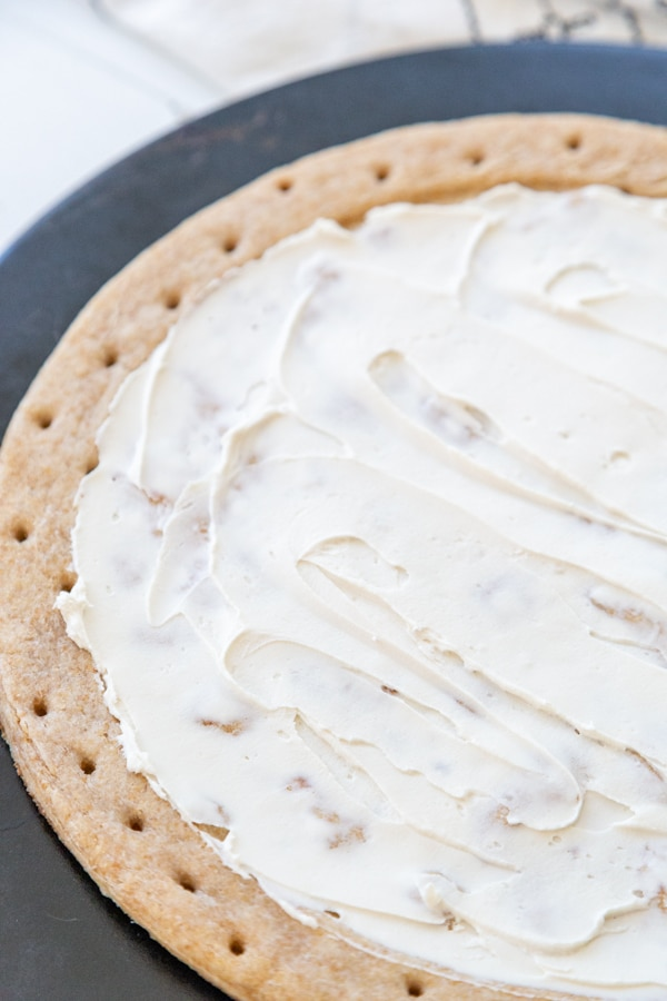 A pie crust on a pizza stone with cream cheese spread on the top.