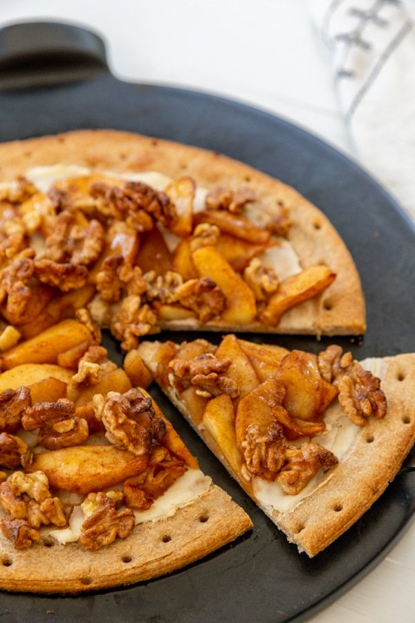An apple pie pizza with a slice cut out of the pie on a black pizza stone.