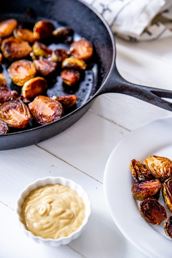 An iron skillet with roasted Brussels sprouts and a white plate of sprouts and a white bowl of dip.