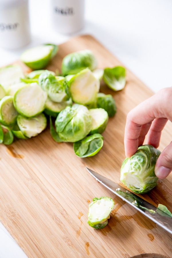 Two hands cutting the end off of a Brussels sprout.