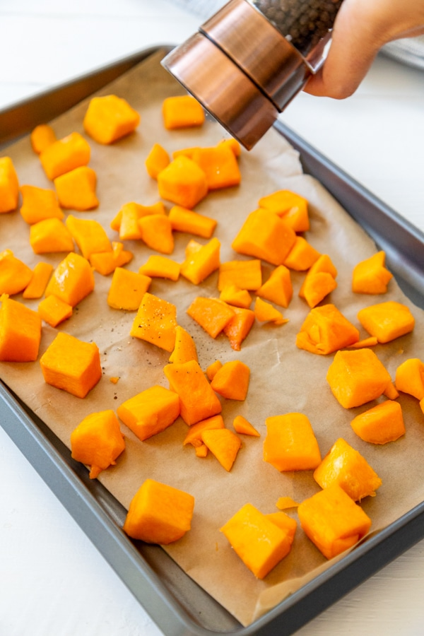 A hand grinding black pepper over cubed squash on a baking sheet.