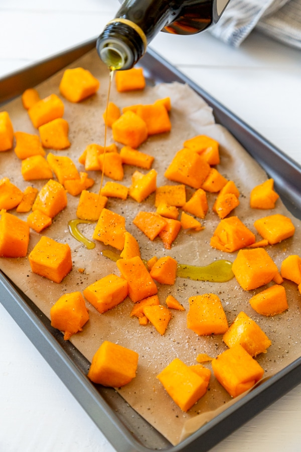 Cubed squash on a parchment lined baking sheet with a hand drizzling olive oil on it.