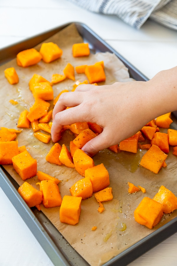 A hand tossing oil on cubed squash on a baking sheet.