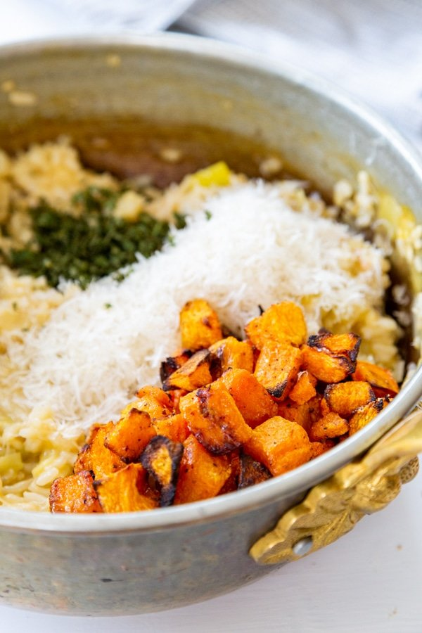 A copper pot with risotto, squash, parmesan, and herbs.