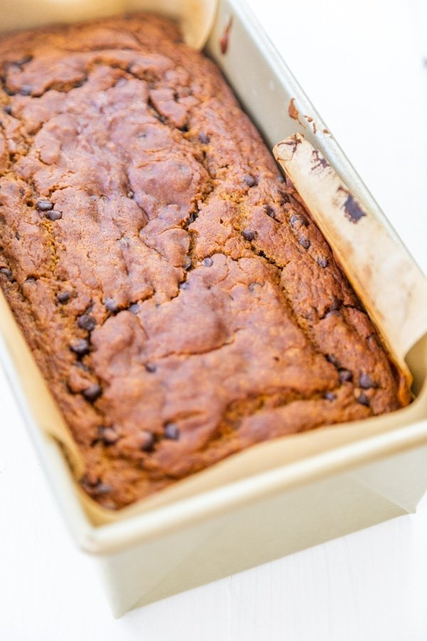 A loaf of chocolate chip pumpkin bread in a bread pan with parchment paper.