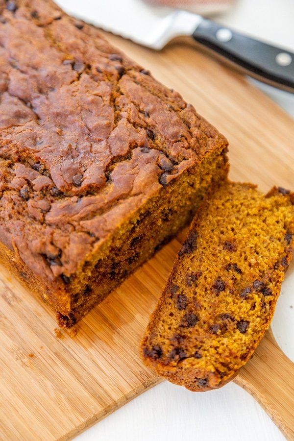 A slice of chocolate chip pumpkin bread and the loaf of bread on a wood board.