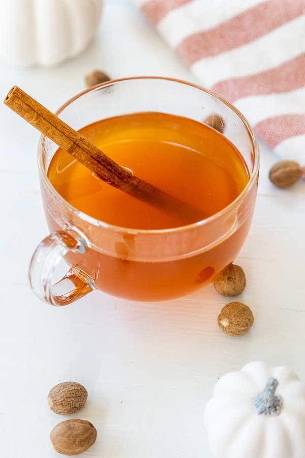 A clear glass mug of mulled apple cider with a cinnamon stick and white pumpkins, spices, and a towel on a white table.
