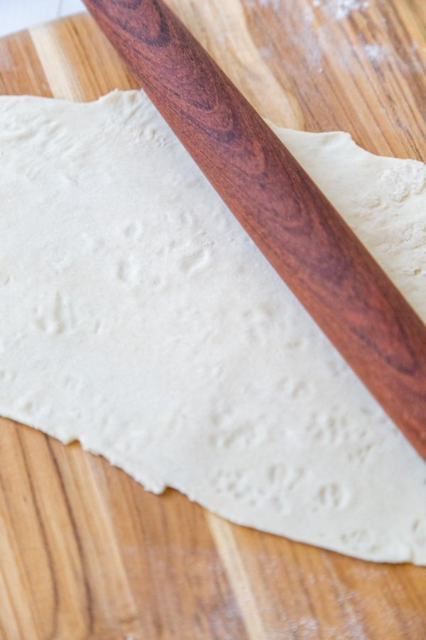 Pasta dough rolled out with a wood rolling pin on a wooden board.