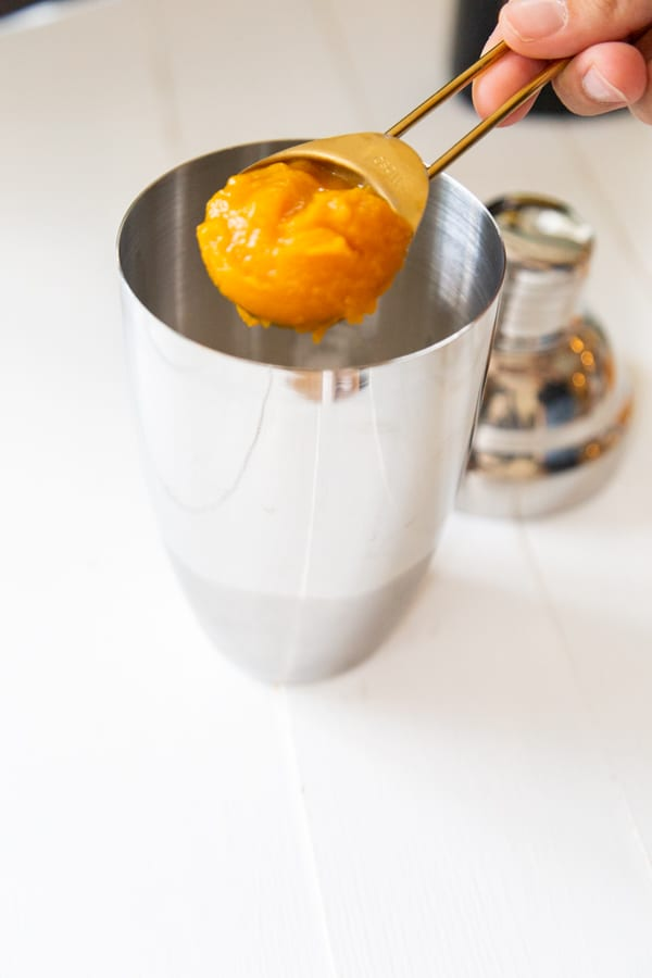 A hand putting a spoonful of pumpkin puree into a martini shaker.