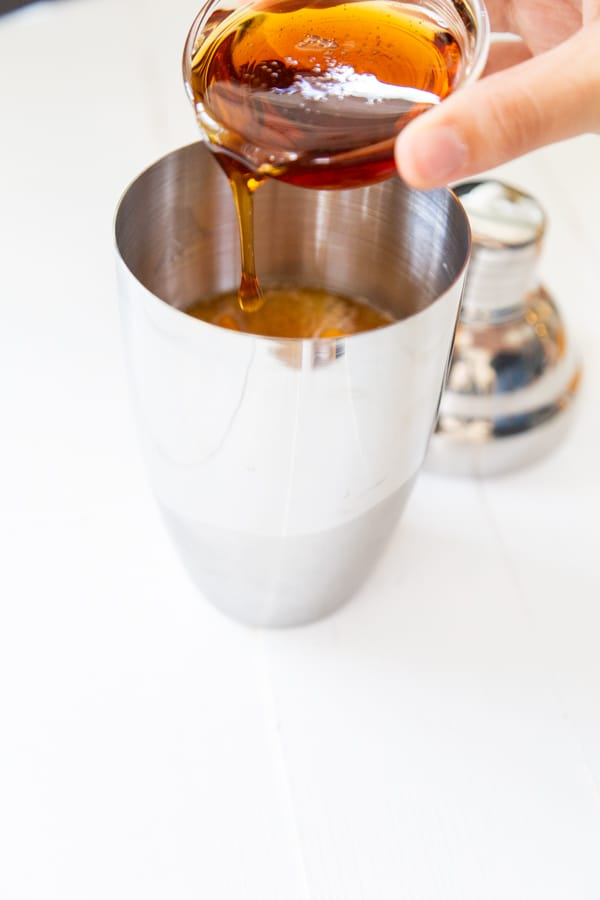 A hand pouring maple syrup into a martini shaker.
