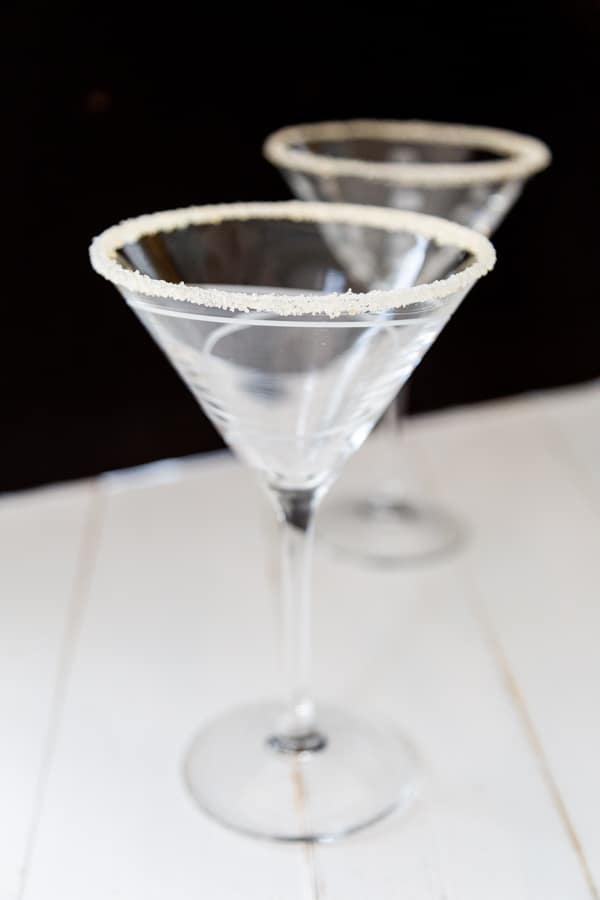 Two empty martini glasses with sugar on the rims.