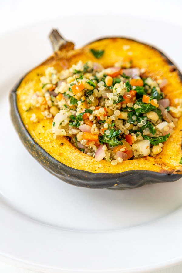 A close up picture of stuffed acorn squash on a white plate.